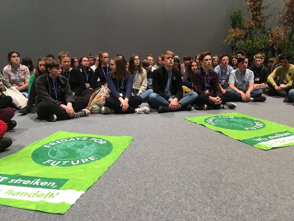 Fridays for Future activists sitting on the floor in protest at COP25