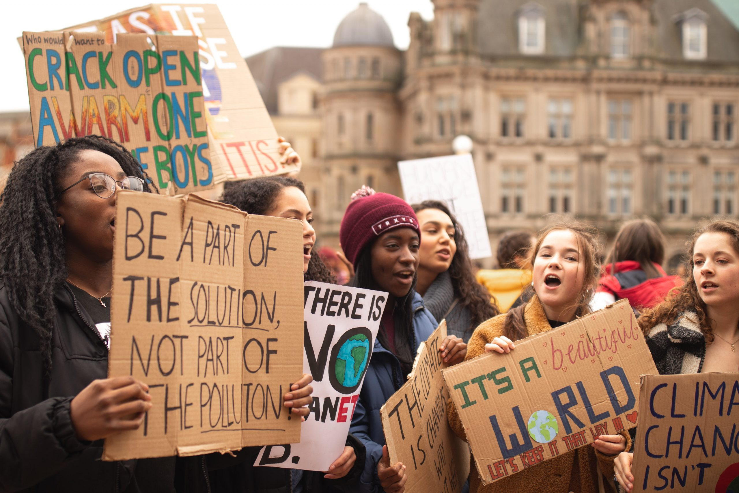 Young people protesting with handmade cardboard placards at a climate protest